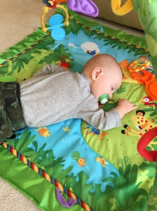 So tired from not sleeping at night that he passed out on his playmat